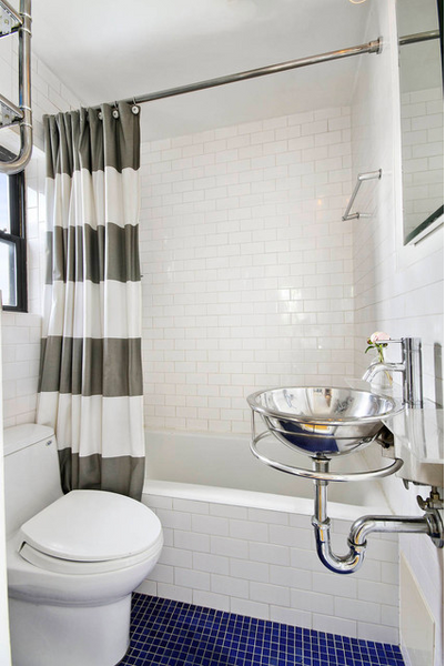 small bathroom with white subway tile, blue tile floor, white and gray striped shower curtain, freestanding metal sink... 5 Steps to Make Your Small Shower Look Bigger Without Remodeling from Bathroom Bliss by Rotator Rod