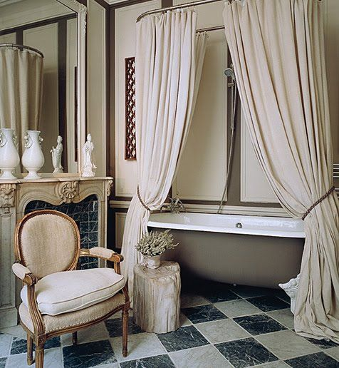 Beautiful Bathroom With Freestanding Bathtub, Double White Shower Curtains,  Fireplace, Chair.