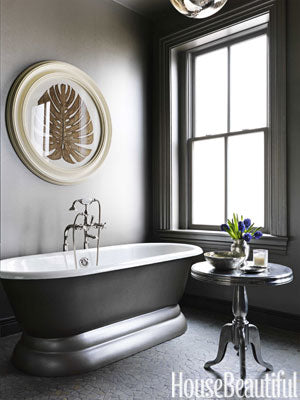 dramatic dark gray bathroom with artwork, freestanding bathtub, & small table with purple flowers... Bathroom Design Trends: Gorgeous Gray Inspiration