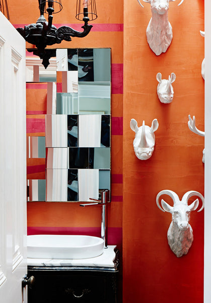 fun contemporary orange bathroom with mirror and white ceramic animal head statues... Beautiful Bathroom Inspiration: Orange Bathrooms from The Bathroom Bliss Blog by Rotator Rod, the original curved shower rod that rotates!