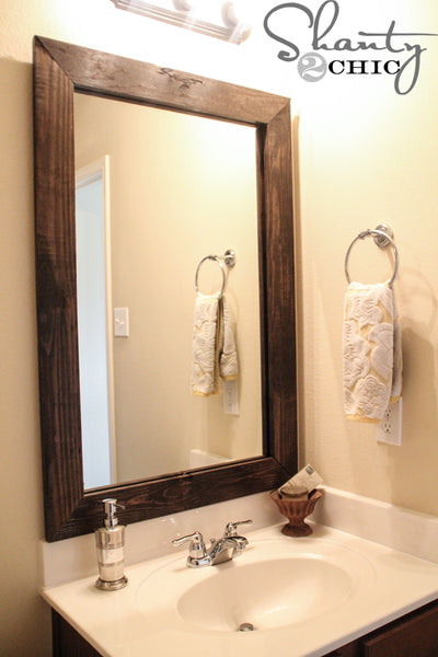 DIY dark wooden bathroom mirror frame in small bathroom... Easy Bathroom Updates for a More Luxurious Rental Apartment