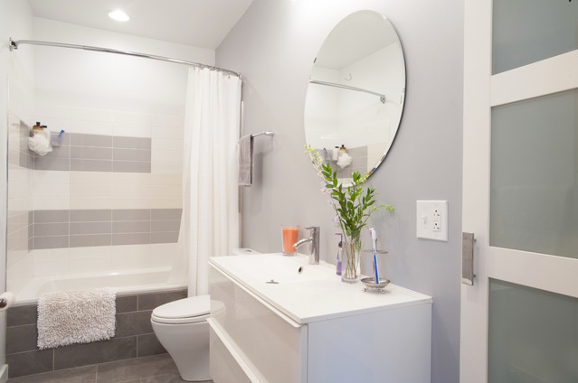 beautiful gray and white bathroom featuring a curved shower rod... Hottest Space-Saving Bathroom Trends for 2015 from The Bathroom Bliss Blog