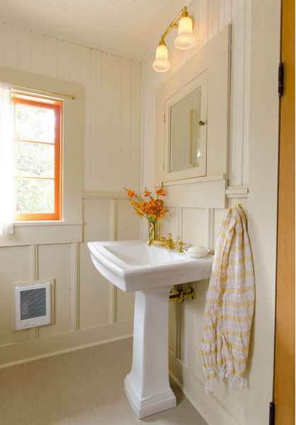 cream colored bathroom with wainscoting, pedestal sink, and orange accents and flowers... Hottest Space-Saving Bathroom Trends for 2015 from The Bathroom Bliss Blog