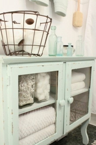 beautiful guest bathroom detail of mint green cabinet with glass doors, fluffy towels and other essentials... Prepare for Holiday House Guests with a Well Stocked Guest Bathroom from The Bathroom Bliss Blog by Rotator Rod