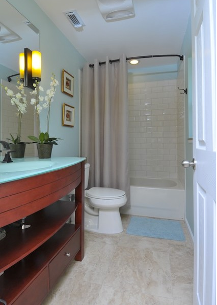 beautiful light blue bathroom with cherry wood cabinets, white orchid, light shower curtain, dark shower rod... Should You Change Your Shower Rod for Winter? from Bathroom Bliss by Rotator Rod