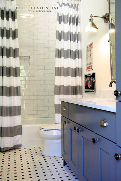 small white bathroom with blue bathroom cabinets, gray and white striped shower curtain, baseball signs... Small Bathroom Chic: Small Spaces with Big Style from Bathroom Bliss by Rotator Rod