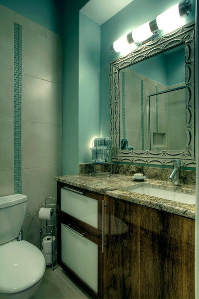 beautifulsmall bathroom with blue accents, wood cabinets, granite countertop, framed mirror... Tiny Bathroom, Big Ideas: 5 Space Saving Ideas for Small Bathrooms by Tradewinds Imports from The Bathroom Bliss Blog by Rotator Rod