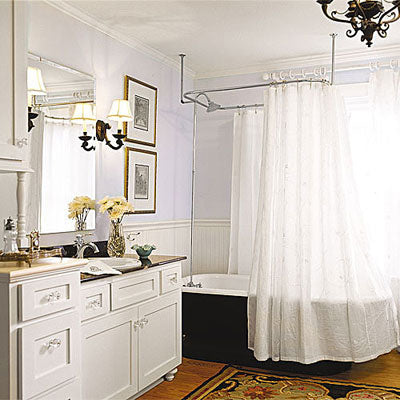 airy, bohemian bathroom with a white shower curtain, black claw foot bathtub, wood floor, yellow flowers, persian rug... Trending in Bathroom Decor: Airy, White Shower Curtains from Bathroom Bliss by Rotator Rod