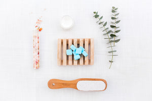 Blue shower tablets sitting on wooden platform surrounded by shower brush, candle and plant