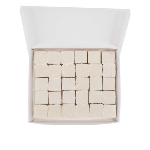Overhead shot of open rectangular container with 5x6 rows of white, shampoo tablets