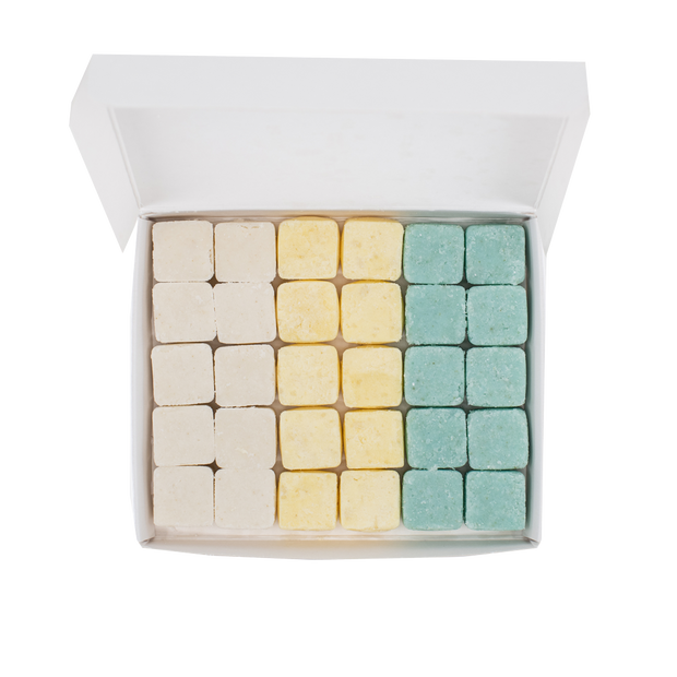 Overhead shot of open rectangular container with 10 tablets each of shampoo, conditioner and body wash