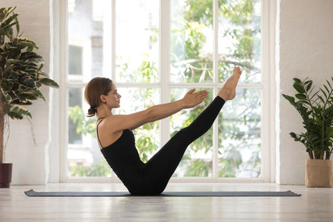 A woman dressed in black workout clothes, practicing a yoga position in her home