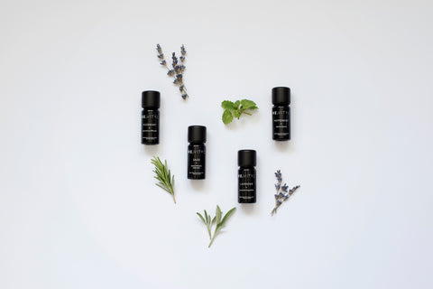 4 organic essential oils and plants laid on a plain light background