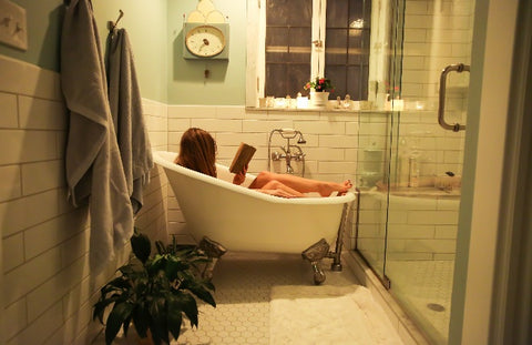 Woman sitting in a relaxing bath reading a book with candles on the window sill.