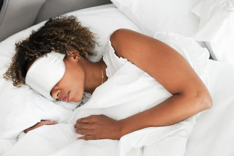 A sleeping woman wearing a sleep mask infused with crystals for insomnia.