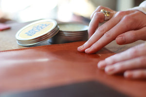 hands applying prodcut to leather