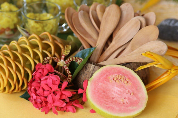 Pink guava displayed with flowers and wooden spoons