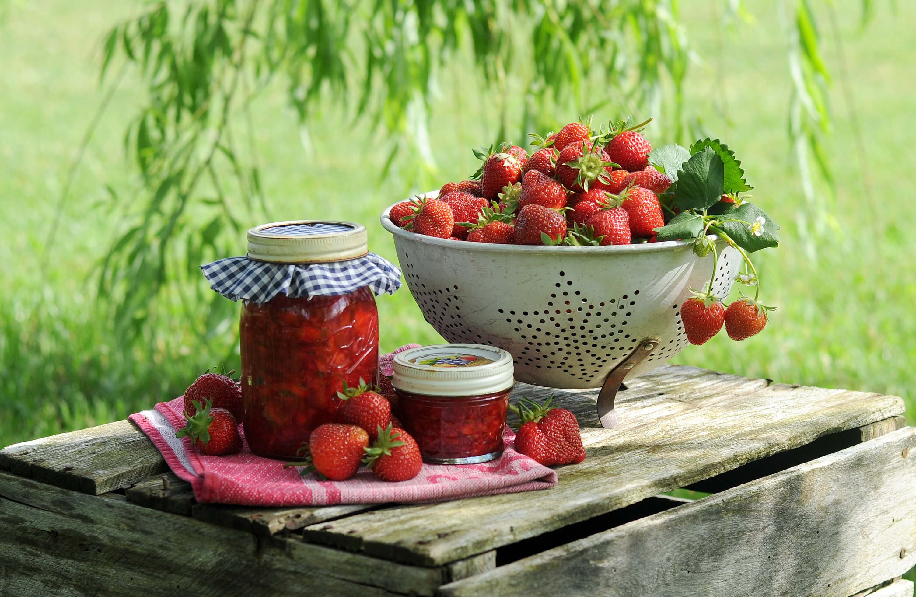 Fresh strawberries and jars of strawberry jam on a table outdoors