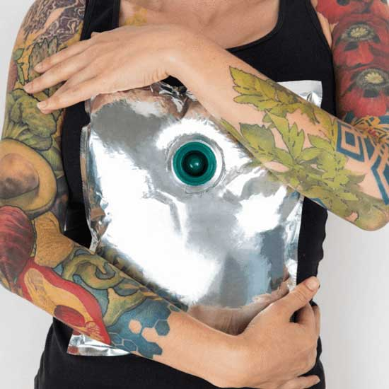 Tattooed person holding an aseptic fruit puree bag