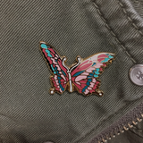 Tattered wings butterfly pin on green khaki jacket