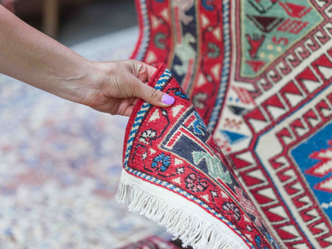 Lady touching an oriental rug to feel its texture