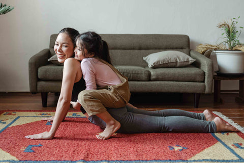 Mom and daughter playing on woven rug