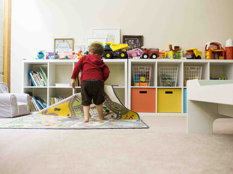 A child play on an area rug in his playroom