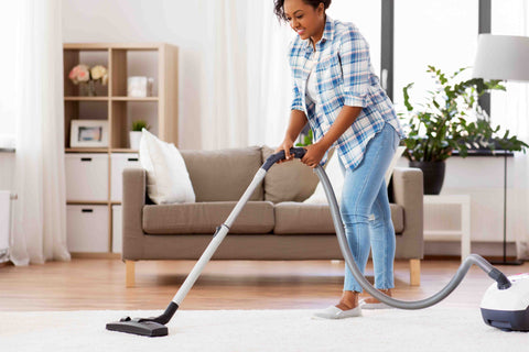 Lady vacuuming an area rug