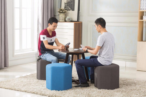 Two men seating on an ottoman in an office lounge