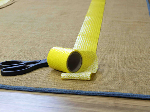 An area rug gripper sticking to the back of a rug