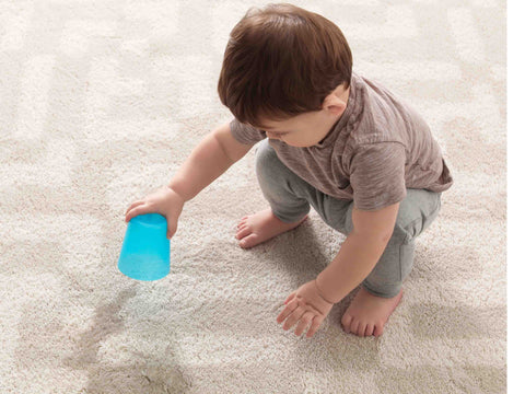 baby pouring water on an area rug
