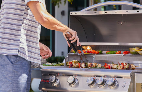 Dad cooking vegetable and meat skewers on Blaze Professional 5 Burner BBQ Grill