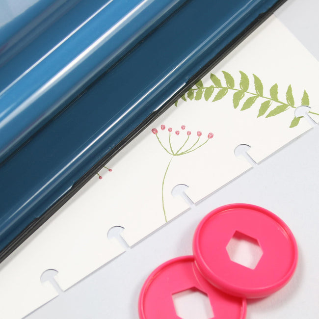 Busy_Days Punch_Gallery_2 Blue edge of Busy Days craft hole punch next to pink plastic rings on decorative planner paper