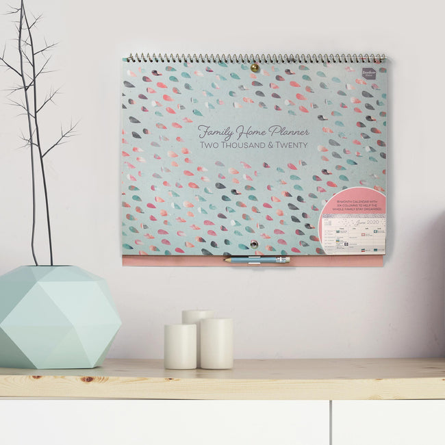 The large Family Home Planner 2020 calendar displayed on a grey wall above a white sideboard with white candles and house plant