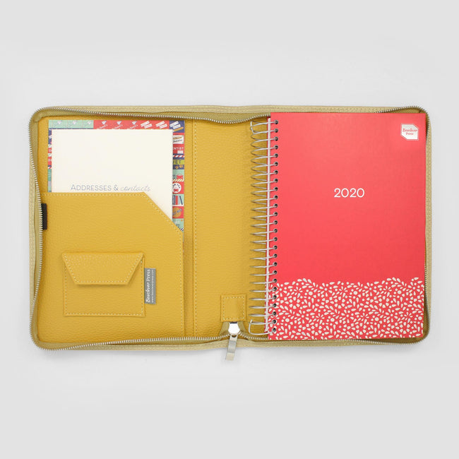 Mustard yellow diary cover on grey background with pocket on the right side and two paperwork pockets on the left