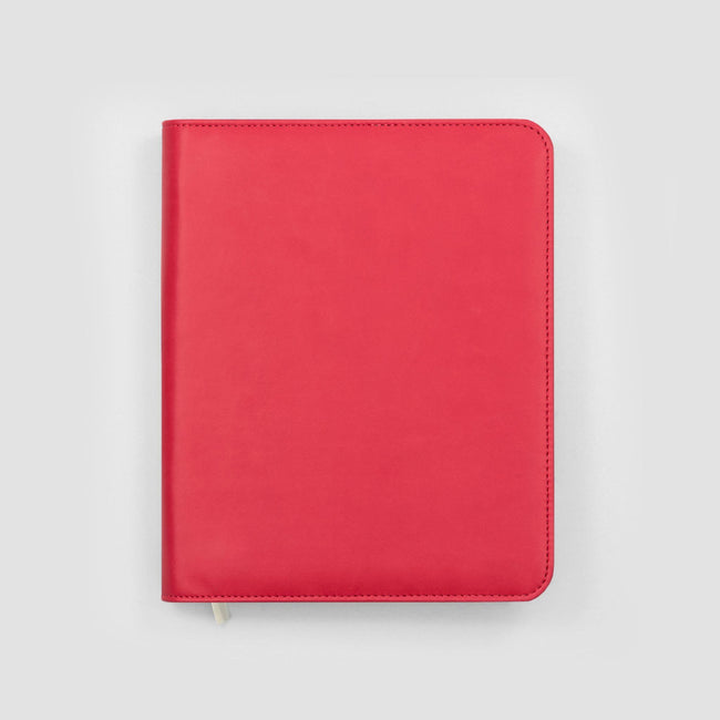 Strawberry rose pink red faux leather diary cover with rounded corners and silver zip detail sat on grey background