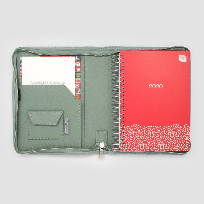 Red diary with foil detail sat in sage green zip around diary cover next to coloured stickers and address book