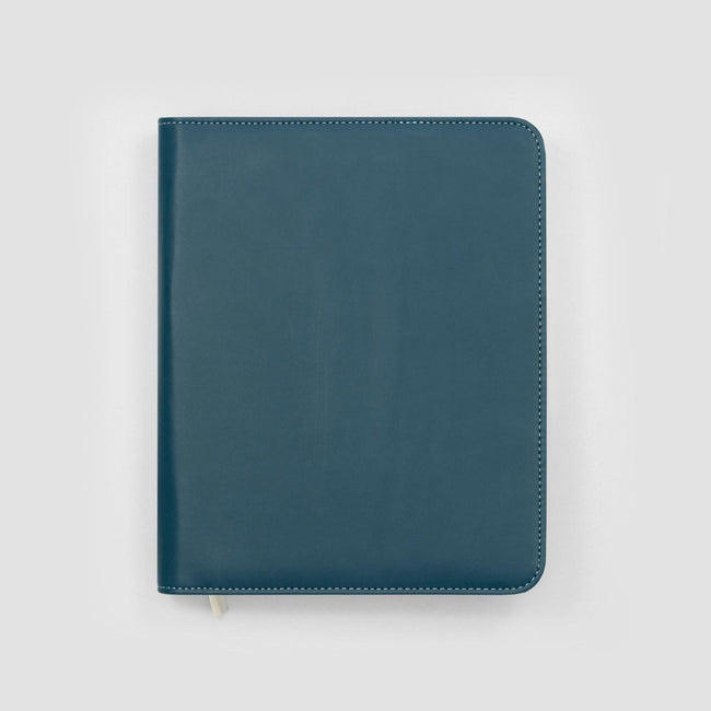 Mid blue A5 faux leather diary cover from Boxclever Press with rounded corners, silver zip sat on grey background