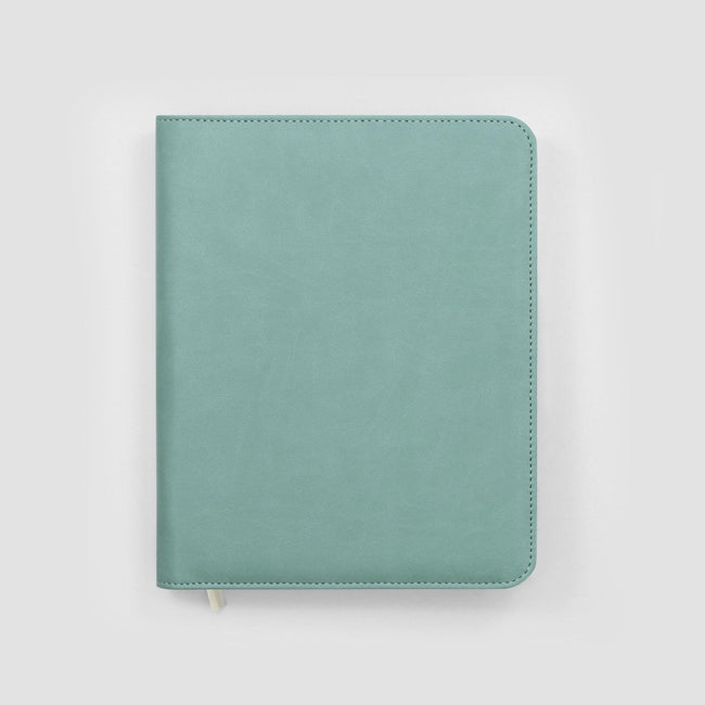 Light blue faux leather diary cover with silver zip and rounded corners sat on a pale grey background