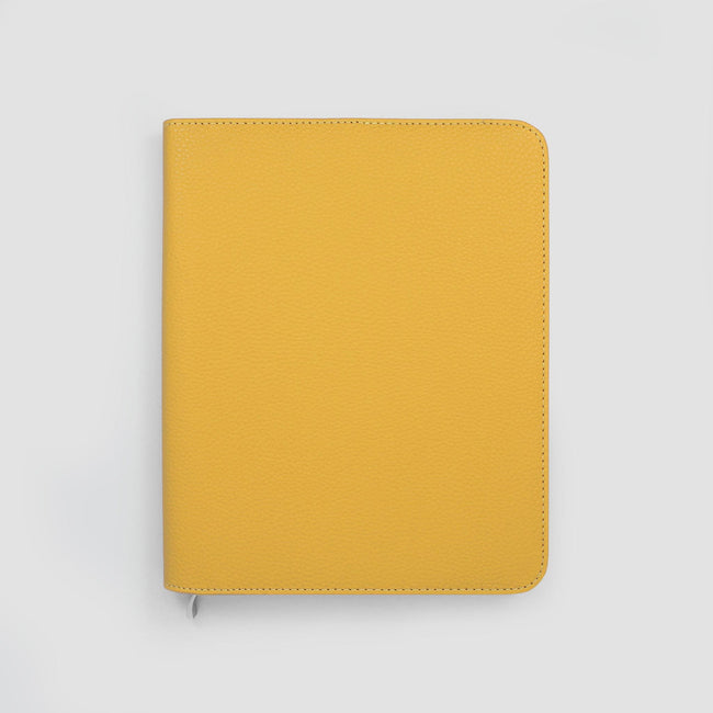 Mustard yellow diary cover with rounded corners on a grey background with silver zip