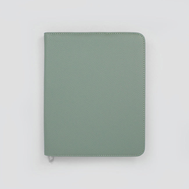 Light sage green diary cover with rounded corners and textured finish showing silver zip for medical professionals