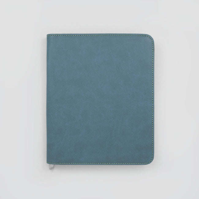 Mid colour blue diary and planner cover with zip around finish and rounded corners on grey background