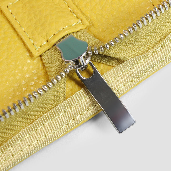 Close up of silver zip on mustard yellow cover