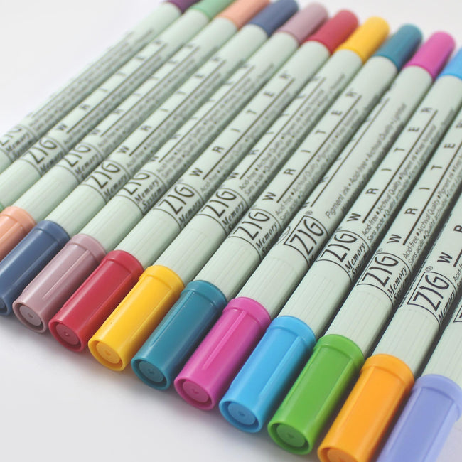 PEN_ZIG_Gallery_1 Zig writing pens in a variety of colours lined up on a pale grey background