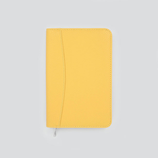 Slimline mustard yellow diary cover with textured finish and contrast stitching with silver zip on grey background