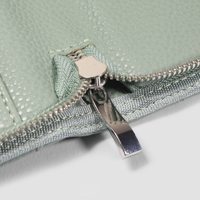 Close up of the silver zip on an open sage green small diary cover