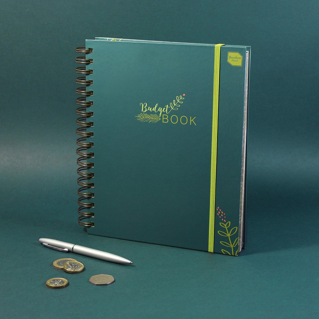 Dark green family accounts book stood on a green background with coins and a silver pen