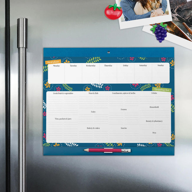 Family magnetic shopping list decorated in a blue affixed to a silver metallic fridge with magnetic strips