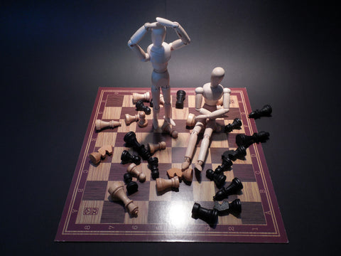 two mannequins and a chess board with pieces