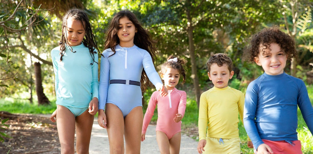 Boys and Girls walking in forest wearing UPF50+ swimwear by NED swim in unisex colours